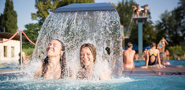 Zwei junge Frauen unter Wasserfall im Außenbecken