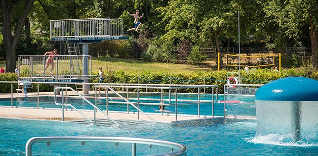 Kinder springen in Freibad von Sprungtürmen