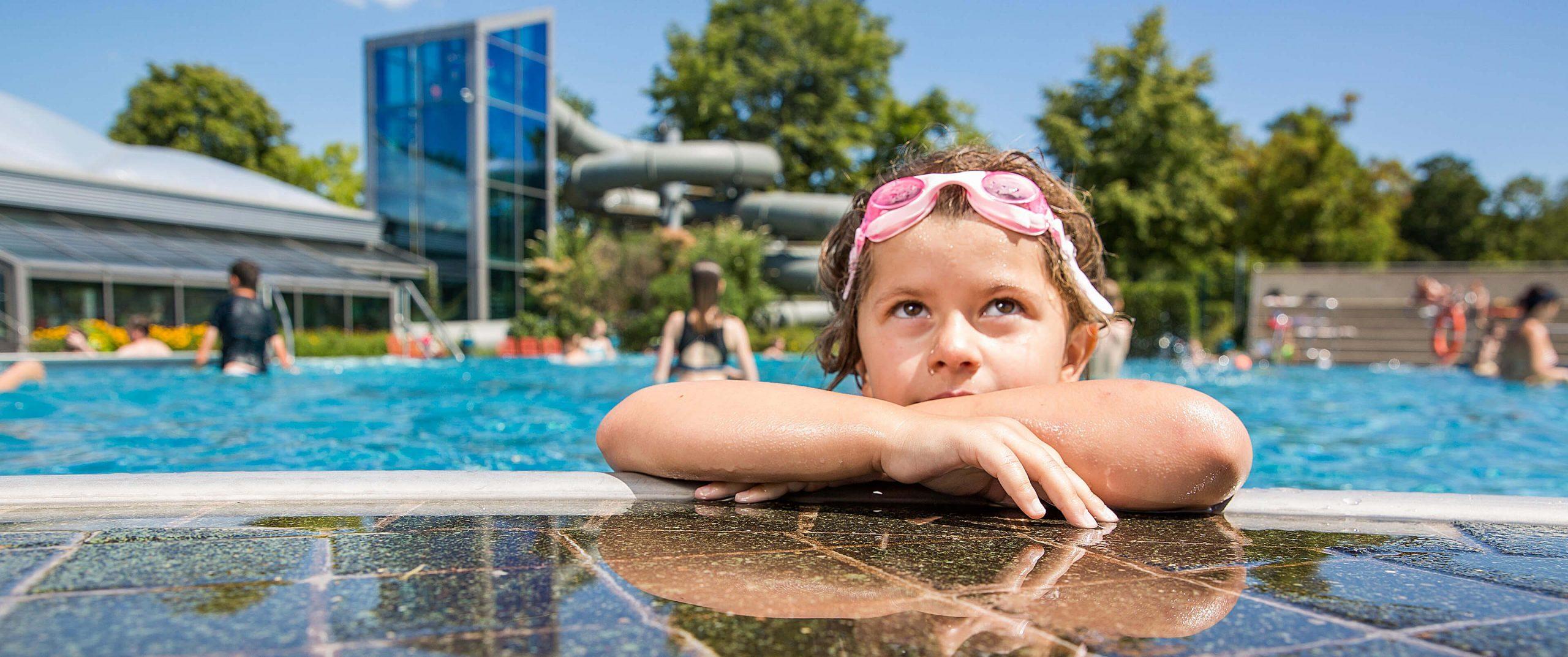 Kind mit Schwimmbrille am Beckenrand